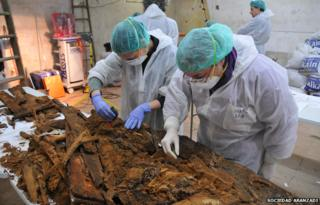 Experts examine the remains of coffins at a table inside the crypt of Madrid's Trinitarian convent in this handout picture released by Madrid's City Hall January 26, 2015