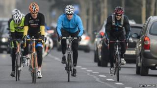 John Kerry, wearing an orange helmet, riding with his bodyguards on Monday 16 March