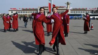 Two Chinese hostesses dance during the third session of the 12th National People's Congress outside the Great Hall of the People in Beijing on 8 March 2015