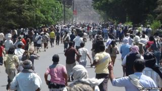 Residents of Aden run towards a weapons depot to take up arms in preparation for a potential advance on the southern Yemeni city by Huthi Shiite militia and their allies on 25 March 2015.