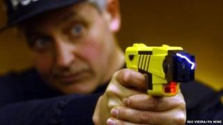 A policeman demonstrates a Taser
