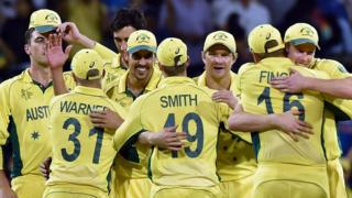 Australia's cricket team players hug each other to celebrate their victory