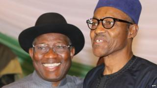 """Nigerian President Goodluck Jonathan (L) and APC main opposition party""""s presidential candidate Mohammadu Buhari (R) smile after signing the renewal of the pledges for peaceful elections on March 26, 2015 in Abuja."""