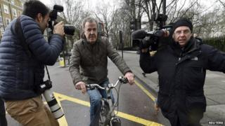 Jeremy Clarkson leaves his home in west London on a bike, followed by photographers