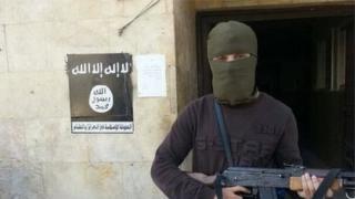 Abu Qa'qa holding a gun, with his face covered