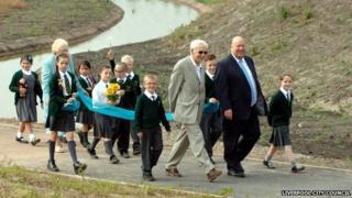 Joe Anderson and children walk through Alt meadows