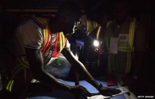 Election officials start the counting process at a polling station in Yenagoa on 28 March
