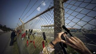 Protesters against the relocation of US Marine Corps Air Station Futenma ties black and red ribbons on the fence of Camp Schwab, an American base near a planned relocation site, in Nago, Okinawa Prefecture Monday, 23 March 2015