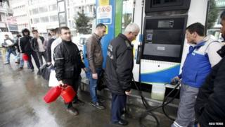 People line up for fuel at a petrol station in Istanbul