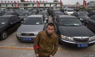 A security guard standing in front of hundreds of government cars due to be auctioned off