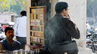 An Indian cigarette and tobacco products vendor looks on as one of his customers takes a puff on his cigarette in New Delhi