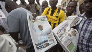 Nigerians pick up the morning's newspapers at a street stall in Kano, Nigeria