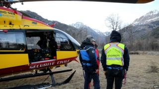 French gendarmes and rescuers stand near a helicopter on April 1, 2015 in Vallouise, in the French Alps