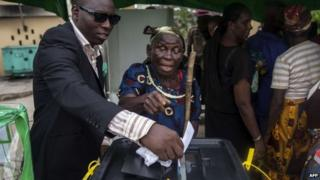 An elderly Nigerian voter is helped to cast her ballot in Otuoke on March 28, 2015