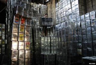 A labourer takes down tin boxes inside a tin container recycling factory in a slum area in Mumbai January 12, 2015.
