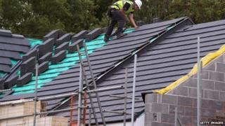 Construction site worker adds roof tiles to a housing development
