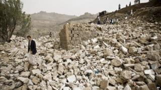 Yemenis stand amid the rubble of houses destroyed by Saudi-led airstrikes in a village near Sanaa, Yemen, 4 April 2015