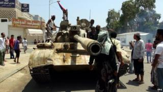 Tribal militiamen loyal to the Yemeni President gather beside a tank during clashes with Houthi fighters in the southern port city of Aden, Yemen, 2 April 2015.