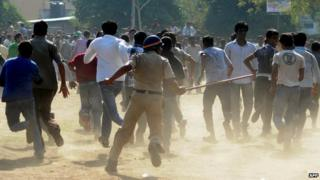 An Indian police office runs towards a crowd with his baton