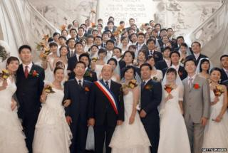 Forty Chinese married couples are pictured after the confirmation of their wedding by Tours' mayor Jean Germain (C), 09 October 2007 in Tours, France