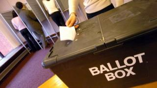Woman posting her paper into ballot box at polling station
