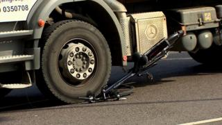 The cycle trapped under the wheels of the lorry