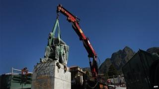 A picture taken on 9 April, 2015 shows the statue of British colonialist Cecil Rhodes being tied by straps to a crane, before its removal at the University of Cape Town. South Africa's oldest university voted on 8 April to remove the monument from its campus after a month of student protests against a perceived symbol of historical white oppression.