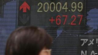 Shares board showing Nikkei above 20,000