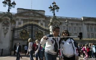 A couple take a selfie in front of Buckingham Palace