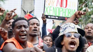 Demonstrators take part in an anti-xenophobic march outside the City Hall of Durban on April 8, 2015