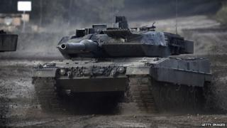 A tank 'Leopard 2A5' of the German Armed Forces rushes through mud and water during an exercise prior the arrival of German Defence Minister Ursula von der Leyen in land operation exercises at the Bundeswehr training ground on 10 October, 2014 near Bergen, Germany
