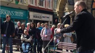 People gathered outside the Caernarfon & Denbigh Herald offices for a rally on Saturday