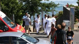 Rescuers and onlookers stand near the beach in Les Aigrettes where the boy was killed on 12 April 2015