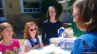 Na'ama Uzan, her mother and a friend serve a customer at the lemonade stand