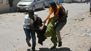 People carry a wounded person at the scene of a car bomb outside the higher education ministry in Mogadishu on Tuesday