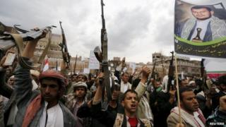Houthi supporters hold up weapons and a picture of Abdul Malik al-Houthi at a rally in Sanaa, Yemen (26 March 2015)