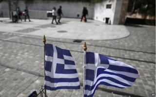 Greek flags flutter as people walk down a central pedestrian street of Athens, 14 April 2015