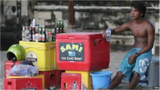 A man sells beer on the beach in Kuta, Bali (15 April 2015)