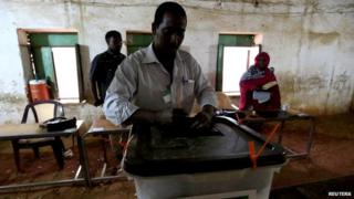 An official closes a ballot box during the end of elections in Khartoum on 16 April, 2015.