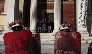 Protesters who have occupied the Athens University, shout from behind as police with their shields covered with red paint face-off against demonstrators during rally by their supporters, in Athens, Thursday, 16 April 2015.