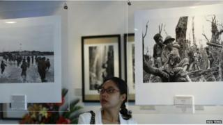 A woman looks at photos of the Vietnam War