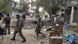 Afghan security forces members inspect the site of a suicide attack near a new Kabul Bank in Jalalabad, east of Kabul, Afghanistan, Saturday, April, 18, 2015.