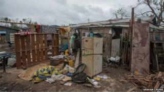 People salvage what they can from their homes in Port Vila, Vanuatu