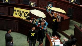 Pro-democracy lawmakers Raymond Chan (2nd R) chants slogans as he and Albert Chan (R), carrying yellow umbrellas, a symbol of the Occupy Central movement, leave to boycott Hong Kong Chief Secretary Carrie Lam during a Legislative Council meeting in Hong Kong April 22, 2015.