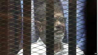 Ousted Egyptian president Mohammed Morsi looks from behind dock bars during trial session, in Cairo