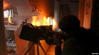 Syrian rebel fires a machine gun during clashes with government forces south of Damascus (22 April 2015)