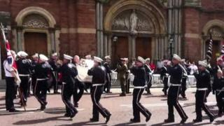 Band members were filmed playing music while marching in circles outside the Catholic church