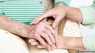Carer holding the hands of an elderly woman