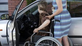 Carer helping woman into car