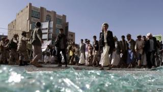 Houthi supporters walk past broken glass at a demonstration in Yemen's capital, Sanaa (22 April 2015)
